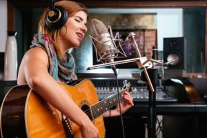 young woman playing guitar in a recording studio
