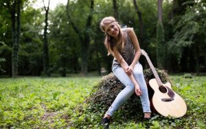 beautiful woman posing with acoustic guitar in the woods